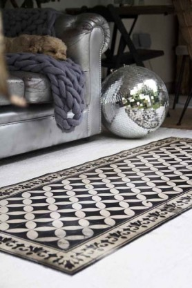 lifestyle image of Beija Vinyl Floor Runner - Sofi Antique on floor with disco balls and grey sofa
