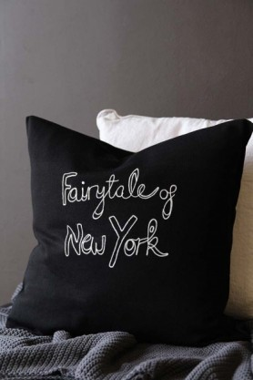 lifestyle image of Bella Freud Merino Wool Fairytale Of New York Cushion on grey blanket and white cushion with grey wall background