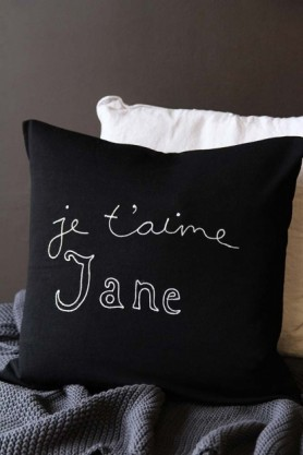 lifestyle image of Bella Freud Merino Wool Je T'aime Jane Cushion on grey blanket and white cushion with grey wall background