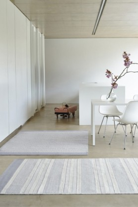 lifestyle image of Belle 100% Wool Rug - GreyNatural Border 06 - 2 Sizes Available in open plan room with white dining table and chairs, a second rug and pale flooring with white walls
