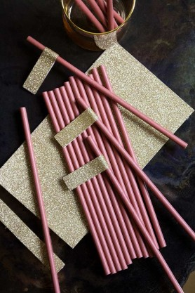 Lifestyle image of the Pack Of 20 Berry Pink Paper Straws With Gold Glitter Tags