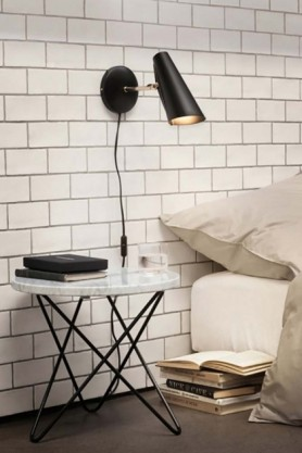lifestyle image of Birdy Wall Light - Black & Brass - Short in bedroom witth white bed and black and white side table on white brick wall background