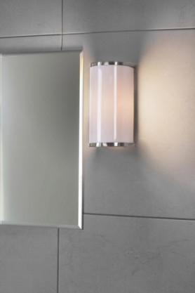 lifestyle image of Bixby Bathroom Wall Light next to mirror and on grey square tile wall background