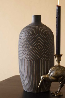 Lifestyle image of the Black African Ceramic Bottle Vase with kiwi candle holder on dark side table and cloisters painted wall background