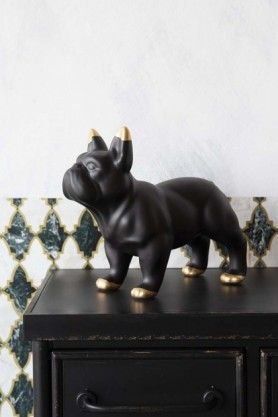 lifestyle image of Black Ceramic French Bulldog Ornament By Young & Battaglia on black desk with patterned wallpaper background