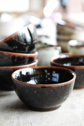 lifestyle image of Black Jolie Stoneware Bowl with other bowls stacked in background on pale table surface