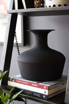 lifestyle image of Black Powder Coated Decanter Vase on pile of books and black shelf unit with picture frame and grey wall background