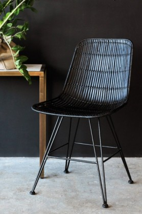 Black Rattan Dining Chair on dark background lifestyle image