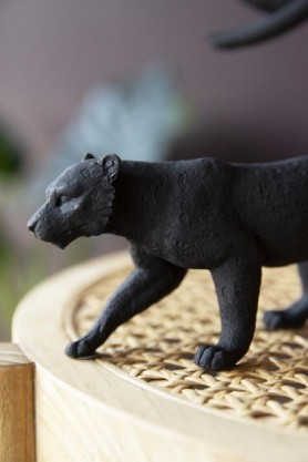Close-up lifestyle image of the Black Stalking Leopard Ornament on wooden and woven stool with plant in background and dark wall