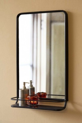 Lifestyle image of the Black Tall Bathroom Mirror With Shelf with bathroom accessories on shelf on cloisters painted wall background