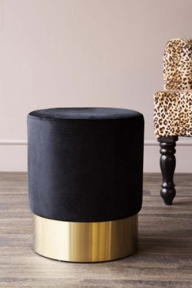 lifestyle image of Black Velvet Pouffe Stool With Gold Base - Small with Rockett St George Leopard Love Armchair in background on wooden floor and pale wall background