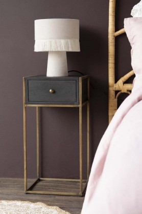 Lifestyle image of the entire Sophos Single Drawer Bedside Table next to a bed with a lamp on top with dark wooden flooring and dark wall background