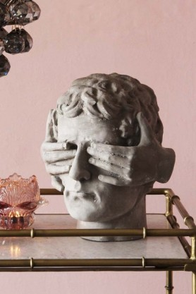 lifestyle image of Blind Faith Stone Effect Head on glass and gold table with tea light holder and plant behind and pink toned wall background