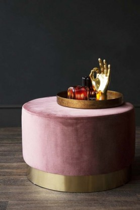lifestyle image of Blush Pink Velvet Pouffe Stool With Gold Base - Large with tray of fruit and OK Gold Hand Ornament on wooden flooring and dark wall background