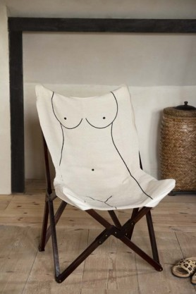 Lifestyle image of the Booby Lady Butterfly Deck Chair with large vase on pale wooden floor and wooden detailed pale wall background