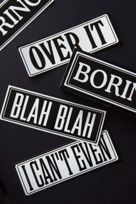 lifestyle image of Boring Typography Stickers overlapping each other on black table background