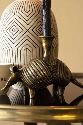 Lifestyle image of the Brass Armadillo Candle Holder on gold side table and candle inside with Stone & Black African Ceramic Bottle Vase in background and cloisters painted wall background