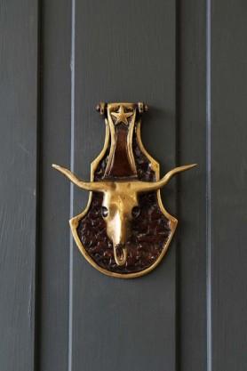 lifestyle image of Brass Bull Skull Door Knocker on grey door background