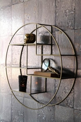 lifestyle image of Brass Circular Shelf Unit filled with ornaments and hung on grey tile wallpaper background