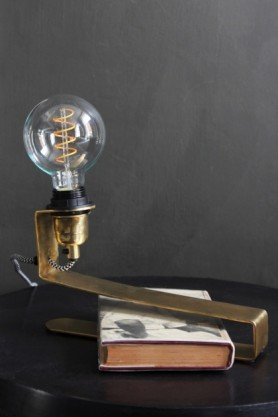 lifestyle image of Brass Clip-On Table Light with book inside clip on black table and grey wall backgropund