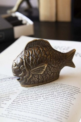 lifestyle image of Brass Effect Fish Tape Measure on open book with tape measure out