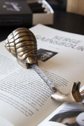 lifestyle image of Brass Effect Snail Tape Measure on open book with tape measure extended