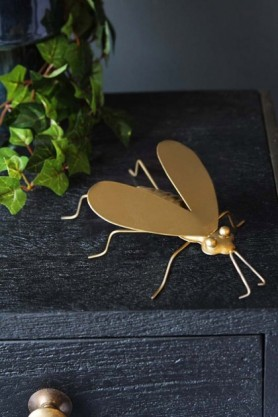 lifestyle image of Brass Fly Ornament on black wooden table with plant behind and dark wall background