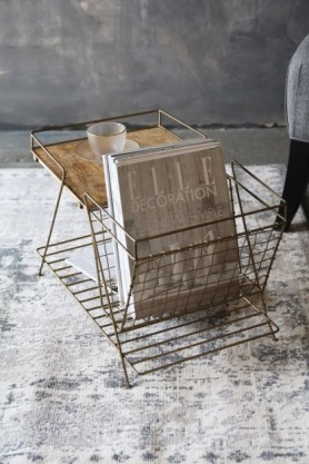 lifestyle image of Brass Magazine Rack with Wooden Shelf with elle magazine inside and glass tea cup and saucer on grey rug and distressed grey wall background