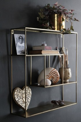 lifestyle image of Brass Quadratic Shelf Unit filled with accessories and hung on dark wall background