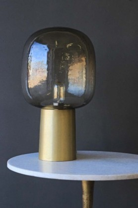 Brass and smoke glass table light featured on a white marble table with dark wall background lifestyle image