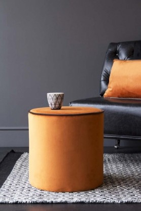 lifestyle image of Burnt Orange Pouffe With Chocolate Brown Piping with glas son top and on grey rug with black leather chair with orange cushion on op and grey wall background