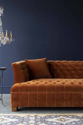 Lifestyle image of Burnt Orange Velvet Chesterfield Sofa with chandelier and rug on floor with dark wall background