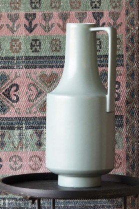 lifestyle image of Ceramic Bottleneck Vase With Handle - Pale Green on black side table with patterned rug hanging in background