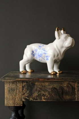 White ceramic bulldog with golden ear tips and paws standing on a marble effect wooden table