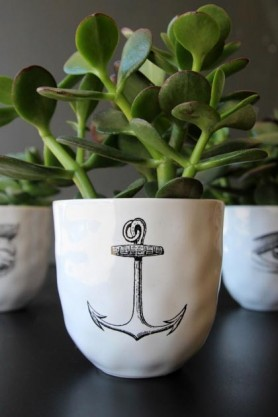 Luscious green plants in a handmade white ceramic cup with a black anchor outline on it
