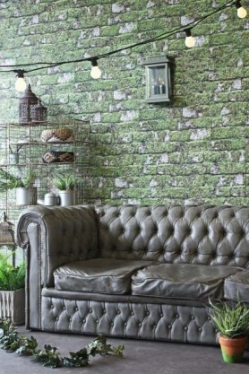 Lifestyle image of Chesterfield Concrete Sofa with chain of festoon lights above and Standing Industrial Brass Storage Rack against distressed green brick wall background