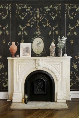 Lifestyle image of the Chinoiserie Panel Wallpaper Mural - Mirto Coal behind white fireplace with decrotive ornaments on top and wooden flooring