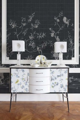 Lifestyle image of the Chinoiserie Tile Wallpaper Mural - Meihua Coal with oriental patterned drawer unit with two white table lmaps on top and wooden flooring