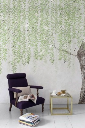 Lifestyle image of the Chinoiserie Tree Wallpaper Mural - Cora Spring with black arm chair with pale cushion on it and small side table and pile of books on white wooden flooring