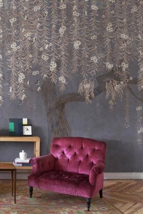 Lifestyle image of the Chinoiserie Tree Wallpaper Mural - Cora Winter with purple tones armchair and wooden side table with blue vases and other ornaments on top on patterned rug and wooden flooring