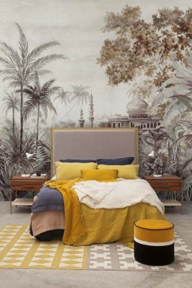 Lifestyle image of the Chinoiserie Wallpaper Mural - Taj Mahal Rose Pink in bedroom with bed with yellow bedding and yellow,black and white pouffe on yellow patterned rug