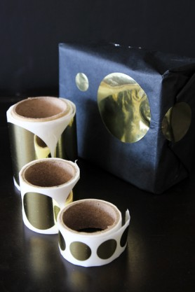 Three rolls of gold circle stickers next to a blue wrapped present with a large gold star on it