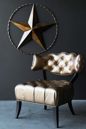 lifestyle image of Cloud Faux Leather Chair - Metallic Gold on grey flooring and large star ornament hanging on dark wall background