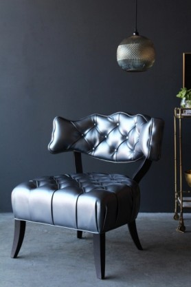 lifestyle image of Cloud Faux Leather Chair - Metallic Pewter with drinks trolley and ceiling light behind on grey flooring and dark wall background