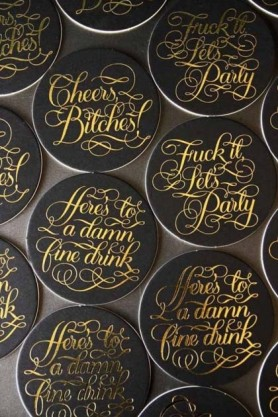 "Black coasters with ""Cheers Bitches"" written in gold on them gathered together on pale background lifestyle image"