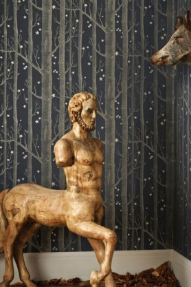 lifestyle image of Cole & Son Whimsical Collection - Colour Woods & Stars Wallpaper - 3 Colours Available with gold centaur statue and donkey head on wall