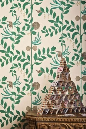 lifestyle image of Cole & Son Whimsical Collection - Secret Garden Wallpaper - 2 Colours Available with card house on wooden table