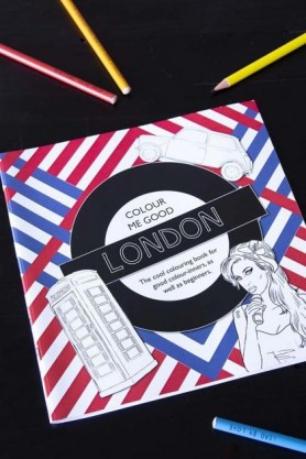 lifestyle image of Colour Me Good London Adult Colouring Book with coloured pencils on black table