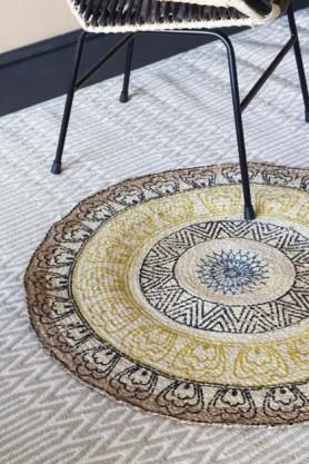 lifestyle image of Colourful Mandala Pattern Natural Jute Circular Rug on grey patterned rug flooring and chair on top