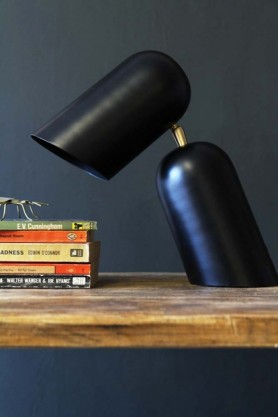 lifestyle image of Como Short Circuit Style Desk Lamp - Black with pile of books on wooden table and dark wall background